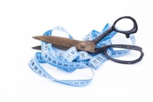 A scissors is cutting a tape measure