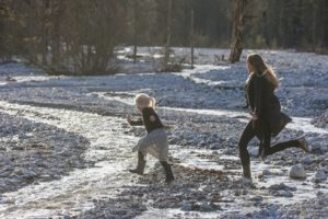 Germany, Bavaria, Lindergriess, mother and daughter running through a brook